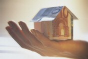 Graphic of hand holding a house made of bank notes